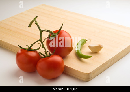 A bunch of tomato, garlic and chili placed on a wooden chopping board. - Stock Photo