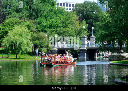 Swan boats in lagoon in Boston Public Gardens with footbridge locateed next to Boston Common - Stock Photo