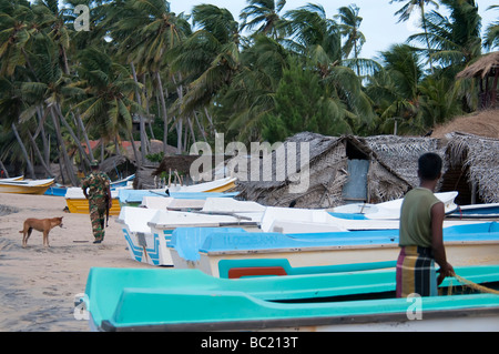 Arugam Bay Sri Lanka fisherman working on the beach armed soldier walking beside boats palm trees fishermen huts - Stock Photo