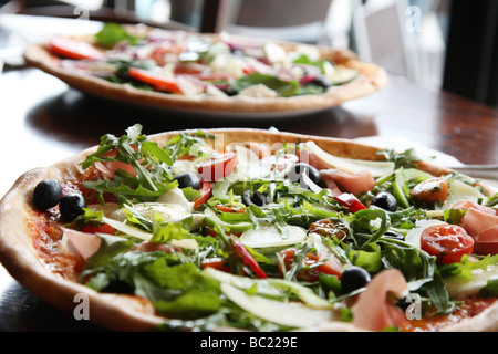 Two pizzas that look tempting and delicious ready for eating. Stone baked thin crust - Stock Photo