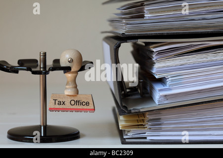 Stamp with inscription Tax Office next to a pile of files - Stock Photo