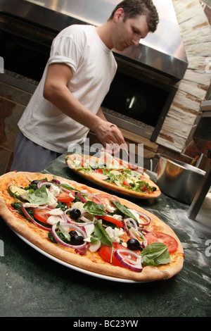 Pizzas topped with delicious looking vegetables made by chef in a restaurant - Stock Photo