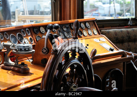 Ships wheel in pilot house of the tall ship Peacemaker with compass, gauges and throttles. - Stock Photo