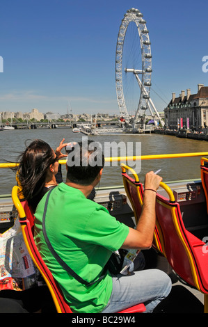 London top deck of open top sightseeing tour bus passengers taking pictures of River Thames and the London Eye - Stock Photo