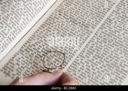 Hand holding a pair of pince-nez eye-glasses over Swedish bible. - Stock Photo