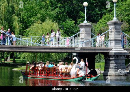 Swan boat passing under foot bridge in Boston Public Gardens located adjacent to the Boston Common Boston, MA USA