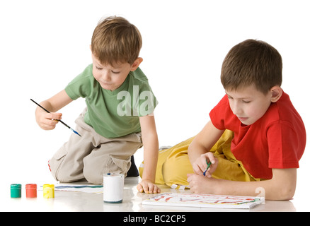 two boys draw with paints sitting on floor isolated on white - Stock Photo