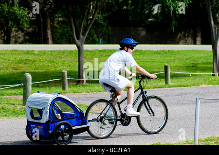 A young mother tows her child in a bicycle trailer in the USA.