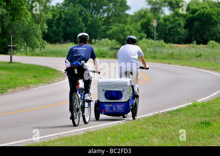 Two parents, a man and woman, ride bicycles on a two-lane road. Mom pulling her child behind her with a bicycle trailer. Oklahoma City, Oklahoma, USA