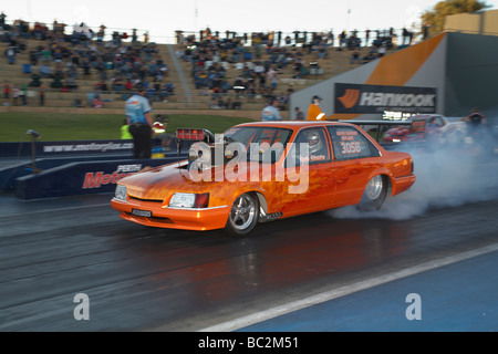 Australian supercharged Holden VK Commodore drag race car performing a tyre smoking burnout - Stock Photo