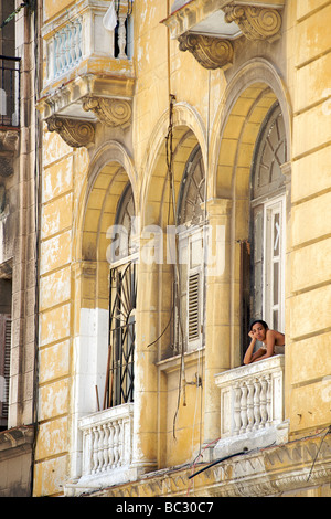 Cuban woman peering from the window balcony of a colonial building in Old Havana, Cuba - Stock Photo