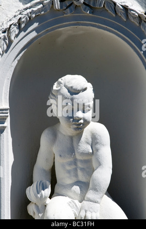 A white statuette of a small boy in an alcove - Stock Photo