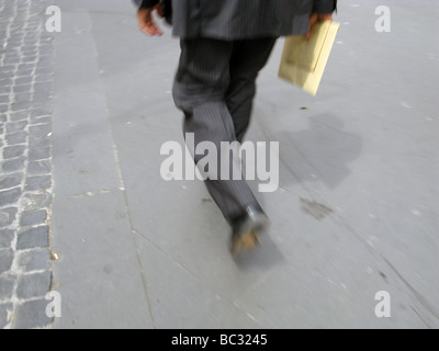 one commuter walking in street in city town - Stock Photo