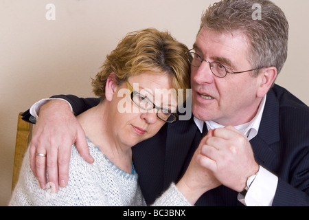 Adult man comforting woman despondent , Portrait of a sad looking couple - Stock Photo