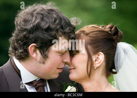 A newly married couple get close to each other and touch noses in a loving embrace - Stock Photo
