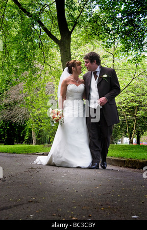 A newly married couple walk through the park talking to each other so they can have their photographs taken - Stock Photo