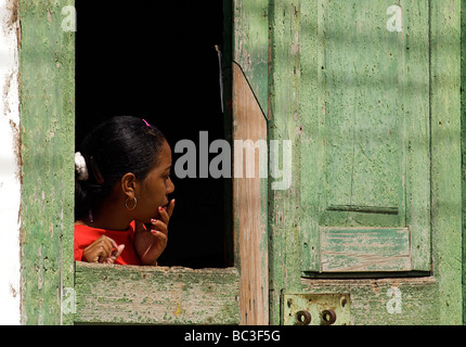 Cuban woman peering from a hatch in the door to her brightly painted colonial home. Trinidad, Cuba - Stock Photo