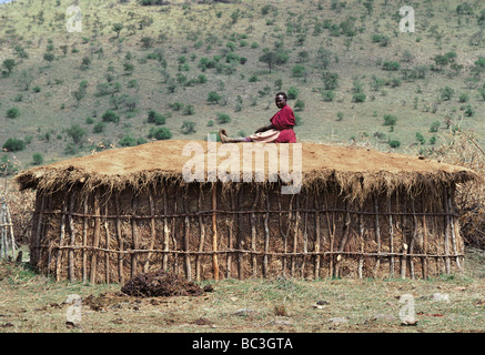 Maasai woman resting on top of her hut after covering it with fresh cow dung Masai Mara National Reserve Kenya Africa - Stock Photo