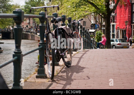 Bicycle parked against an iron railing on a bridge over a canal in Amsterdam - Stock Photo