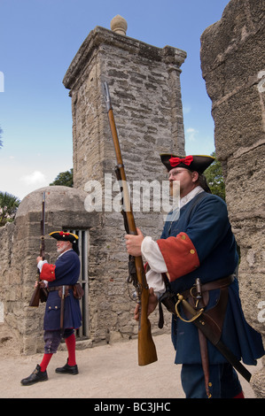 Actors in 18th century Spanish army uniforms carry flintlock rifles as guard historic City Gates St Augustine Florida - Stock Photo