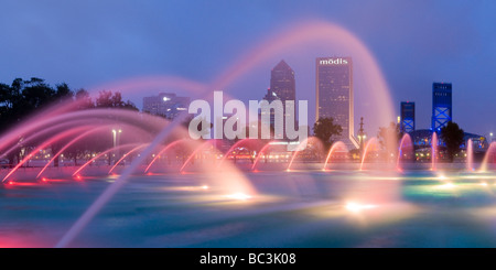 Fountain in downtown Friendship Park frames Jacksonville Florida skyline at dusk - Stock Photo