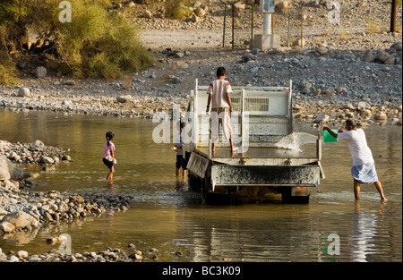 Family cleaning car in Wadi  Ghul Al Dakhiliyah region Oman - Stock Photo