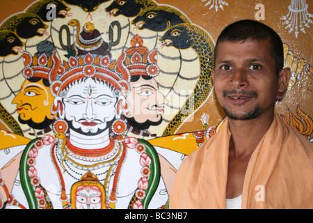 Indian Priest Standing Besiside Painting Of the Trimurti Of The Three Hindu Gods, Jagganath Temple, Koraput, India - Stock Photo