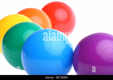 Six shiny coloured plastic toy balls isolated on white. Copy space and room for text available - Stock Photo