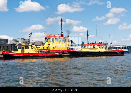 Yellow and red boats belonging to the Port of Amsterdam on the Het Ij - Stock Photo