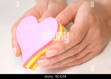 Hands holding heart shaped colorful sticky notes - Stock Photo