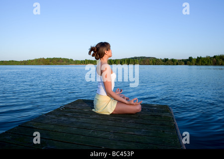 Beautiful young woman doing yoga exercise outdoors - Stock Photo