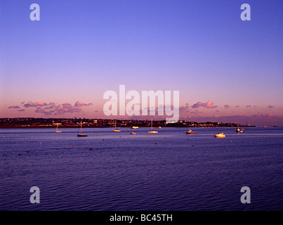 torbay estuary duing a sunset with sea boats in harbour shot from the railway - Stock Photo