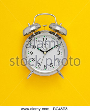 old fashioned bell alarm clock photographed on a yellow background - Stock Photo