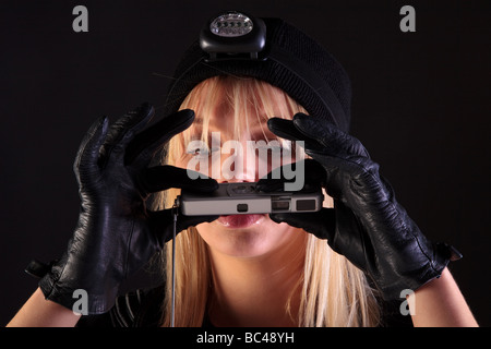 Blond woman cat burglar taking a photo with a spy camera - Stock Photo