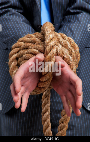 Close up of a businessmans hands tied with rope - Stock Photo