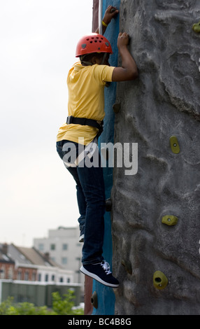 A schoolchild tries some climbing on an army training course. - Stock Photo