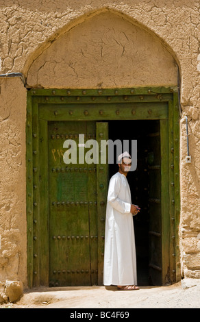 Young local man in front of traditional house made from mud and brick in the town of Al Hamra Sultanate of Oman - Stock Photo