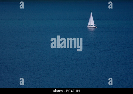 Sailboat isolated in deep blue water - Stock Photo