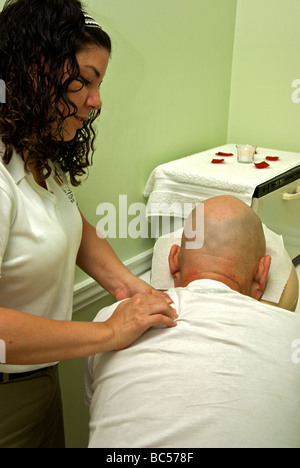 Female massage therapist giving bald male client a deep tissue shoulder treatment - Stock Photo