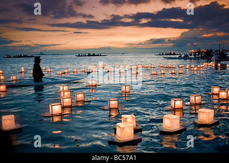 Floating lanterns drift lazily in the water as the sun sets over Honolulu, Hawaii - Stock Photo