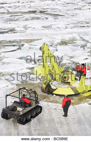 Workers on the Red River wearing survival suits, while repairing an Amphibex Icebreaker, near Selkirk, Manitoba, - Stock Photo