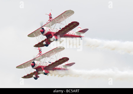 Two barnstorming biplanes fly past in formation with two young women standing upside down on the wing. - Stock Photo