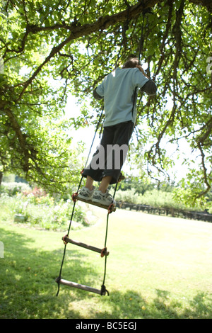 boy climbing up rope ladder in backyard, summer time, rope swing - Stock Photo