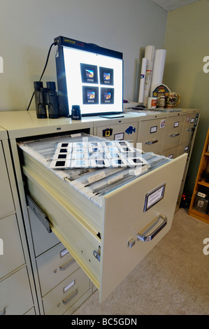File Cabinets Slide Photo Pages Light Box and Loupe in Photographers Office - Stock Photo