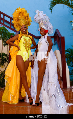 Beautiful dancers in costume against blue wall with headresses in the old colonial city of Trinidad in Cuba - Stock Photo