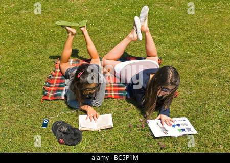 Horizontal aerial portrait of two attractive young girls lying on the grass reading books and listening to an ipod - Stock Photo