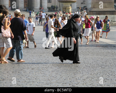 one single nun walking in st peter's square in rome - Stock Photo