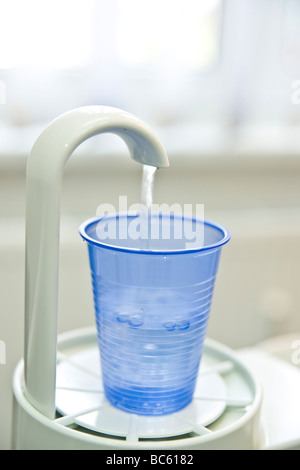 Close-up of disposable cup under water tap in dentist office