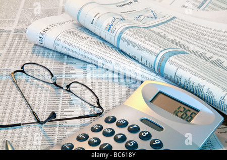 Close-up of financial newspapers with eyeglass and calculator - Stock Photo