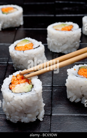shallow focus vertical close up of sushi with chopsticks on a black wooden background - Stock Photo